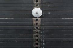 Gammal och använd svart viktbunt med vitnummer i en idrottshall Rostiga plana metallvikter Arkivbild