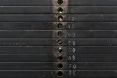 Gammal och använd svart viktbunt med vitnummer i en idrottshall Rostiga plana metallvikter Royaltyfri Foto