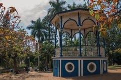 Gammal och färgrik gazebo i en liten fyrkant under grönskande trädgårds- mycket av träd, i en solig dag på São Manuel fotografering för bildbyråer