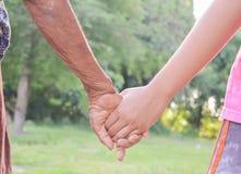 Gammal och för barn` s hand för hand, med ljus Fotografering för Bildbyråer