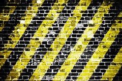Gammal och riden ut grungy tegelstenvägg med fara- eller uppmärksamhetsvart och gula diagonala band som texturbakgrund Royaltyfri Foto