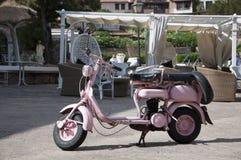 Gammal och rosa lambretta Arkivfoto