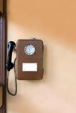 Gammal offentlig payphone på väggen Brun metalltelefon Royaltyfria Bilder