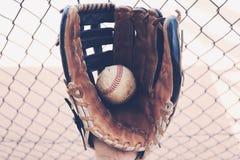 Gammal ojämn baseballhandske i dugout Royaltyfria Foton