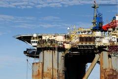 Gammal oljeplattform i hamn Royaltyfria Foton