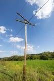 Gammal onödig träelkrafts pylon med brutna trådar Arkivfoton