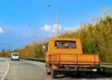 Gammal orange lantgårdnyttofordon - lastbilen på den stenlade landsvägen i Grekland som kör till sidan så någon, kan passera arkivbilder