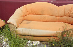 Gammal orange soffa arkivbild