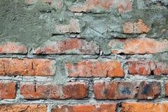 Gammal orange tegelstenvägg med cementlappen och sprickor arkivbilder