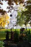 Gammal ortodox kyrka med ett kors till och med höstlövverket mos arkivbild