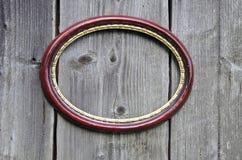 Gammal oval bildram på den forntida träväggen Royaltyfri Bild