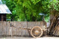 Gammal oxevagn framme av ett burmese hus arkivbilder