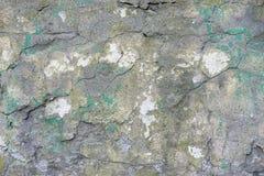 Gammal packad tegelstenvägg med sprickor och spår av målarfärg royaltyfria foton