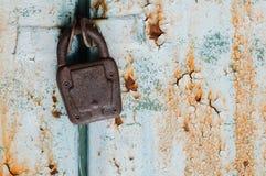 Gammal padlock på rostig dörr Arkivfoton