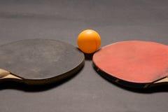 Gammal pingpongskovlar och boll Arkivfoto