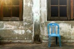 Gammal plast- stol nära den gamla cementväggen royaltyfria bilder