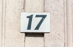 Gammal platta nummer 17 sjutton för metall för tappninghusadress på murbrukfasaden av den övergav yttre väggen för hem på gatasid arkivfoto