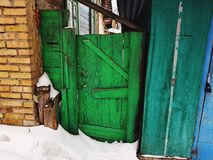 Gammal port med ett staket på ingången till ett tegelstenhus på bakgrunden av den insnöade vintern arkivbilder