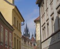 Gammal Prague mittgata med det gotiska kyrkliga tornet Arkivbild
