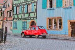 Gammal röd bil i gammal stad Fotografering för Bildbyråer