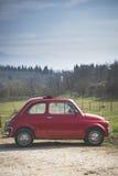 Gammal röd bil i landet Arkivfoto
