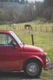 Gammal röd bil och ett tuscan landskap Royaltyfri Bild