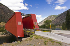 Gammal röd bro över floden Arkivbild