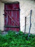 Gammal röd dörr av ett hus Fotografering för Bildbyråer