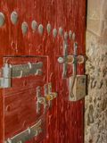 Gammal röd port med falska bultar och låset arkivbild