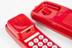 Gammal röd telefon med en telefonlur En telefonuppsättning från ninetiesna fotografering för bildbyråer