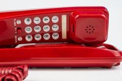 Gammal röd telefon med en telefonlur En telefonuppsättning från ninetiesna arkivfoton
