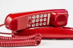 Gammal röd telefon med en telefonlur En telefonuppsättning från ninetiesna royaltyfria bilder