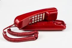 Gammal röd telefon med en telefonlur En telefonuppsättning från ninetiesna arkivbilder