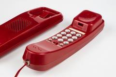 Gammal röd telefon med en telefonlur En telefonuppsättning från ninetiesna royaltyfri bild
