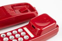 Gammal röd telefon med en telefonlur En telefonuppsättning från ninetiesna royaltyfria foton