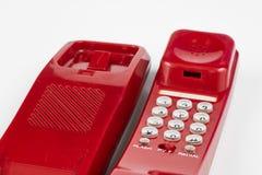Gammal röd telefon med en telefonlur En telefonuppsättning från ninetiesna royaltyfri foto