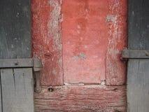 Gammal röd timmer inramade det byggande dörrgångjärnet för blåa grå färger fotografering för bildbyråer