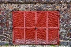 Gammal röd träport med låset i ett stenstaket Royaltyfria Bilder