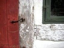 Gammal röd trätimmerdörr med det kalkade järndörrgångjärnet royaltyfri bild