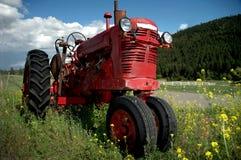 gammal röd traktor för lantgård Arkivfoto
