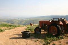 Gammal röd traktor framme av beslag Royaltyfri Bild