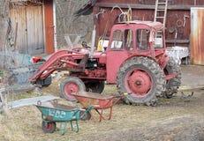Gammal röd traktor och skottkärra Arkivfoton