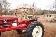Gammal röd traktor på lantgården arkivfoton