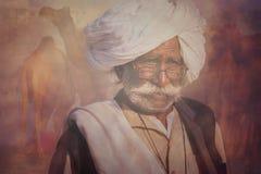 Gammal Rajasthani man mot bakgrunden av hans kamel Royaltyfria Bilder