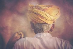 Gammal Rajasthani man mot bakgrunden av hans kamel Arkivfoton