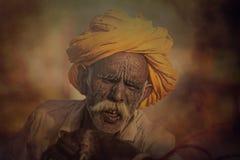 Gammal Rajasthani man mot bakgrunden av hans kamel Royaltyfri Fotografi