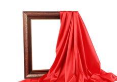 Gammal ram och röd siden- gardin Arkivbild