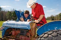 gammal reparerande traktor Arkivfoto