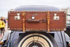 Gammal resväska över hjulet, på stammen av en gammal bil Arkivbilder