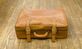 Gammal resväska för tappning på ett trägolv Royaltyfri Foto
